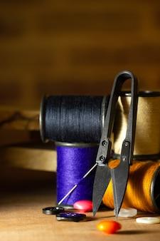 Ago e fili contro le forbici di plastica di taglio del filo e del bottone sulla tavola di legno. chiudi e copia lo spazio per il testo. concetto di sarto o designer.