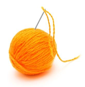 Ago e palla di lana. su un tavolo bianco.