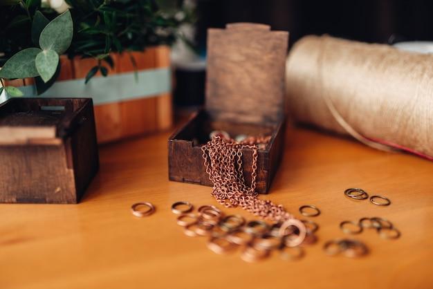 Accessori di ricamo, piccoli anelli di metallo e scatola di legno decorativa sul tavolo, primo piano. gioielli fatti a mano, bigiotteria