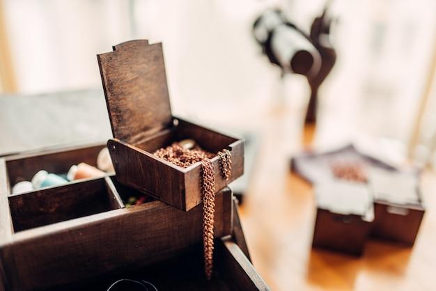 Accessori di cucito, piccoli anelli di metallo in una scatola di legno sul tavolo, primo piano, fuoco selettivo, nessuno. gioielli fatti a mano, bigiotteria