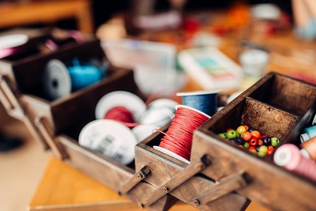 Ricamo, scatola con corde colorate, perline e accessori sul tavolo di legno, nessuno. strumenti artigianali. arredamento di moda fatto a mano