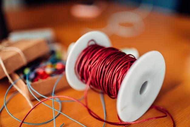 Ricamo, bobina con corda decorativa rossa, primo piano, scatola con perline colorate, accessori sulla tavola di legno, nessuno. strumenti artigianali. accessori fatti a mano