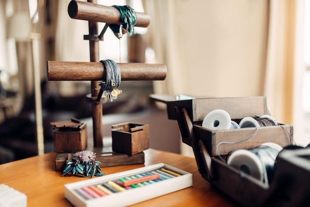 Hobby ricamo, strumenti artigianali, primo piano. attrezzatura di un artigiano, braccialetti fatti a mano e bigiotteria