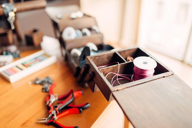 Hobby ricamo, strumenti artigianali, primo piano. luogo di lavoro di un artigiano, bigiotteria fatta a mano