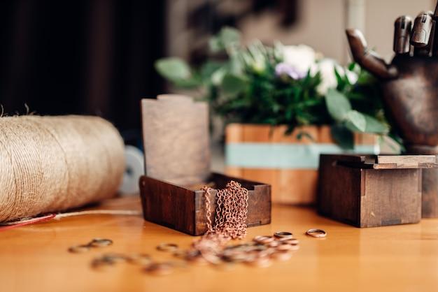 Ricamo, anelli di metallo e scatola di legno sul tavolo