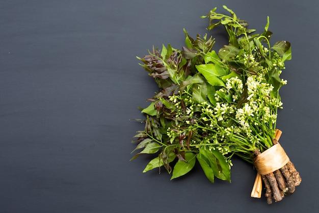 Foglie di neem e fiori su sfondo scuro.