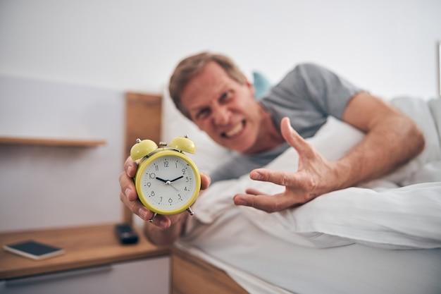Persona di sesso maschile deliziata negativa che arriccia la fronte e dimostra la sua sveglia sulla fotocamera