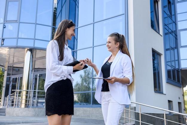 Concetto di negoziazione all'aperto. due giovani donne prima dell'edificio per uffici parlando dei dettagli del contratto
