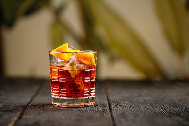 Cocktail negroni in vetro vecchio modo sul tavolo di legno
