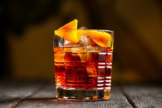 Negroni cocktail con gin nel vecchio bicchiere di moda sullo sfondo sfocato