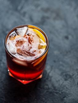 Negroni cocktail con arancia sul tavolo di pietra scura