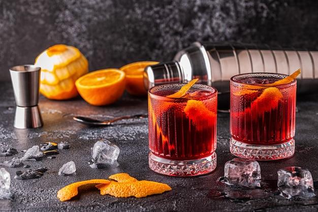 Cocktail negroni con buccia d'arancia e ghiaccio, fuoco selettivo.