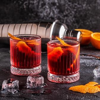 Negroni cocktail con scorza d'arancia e ghiaccio, messa a fuoco selettiva.