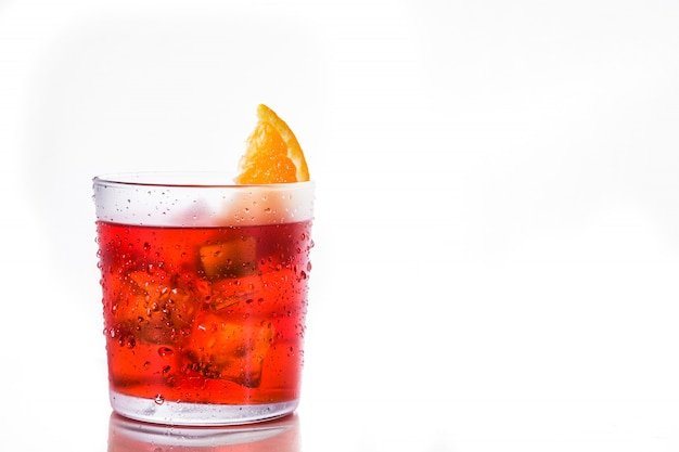 Cocktail di negroni con il pezzo di arancia in vetro isolato su bianco, copyspace