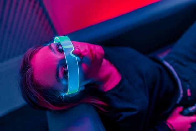 Una luce viola al neon cade su una giovane donna con gli occhiali luminosi. avvicinamento. la foto ha l'effetto di shush, grano.