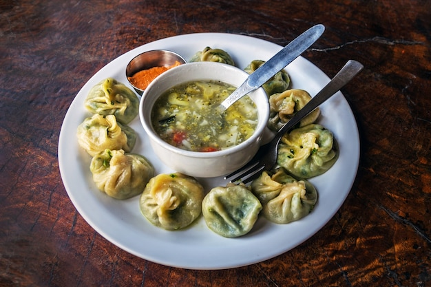 Momos tradizionali nepalesi serviti con chatni di pomodoro e zuppa calda