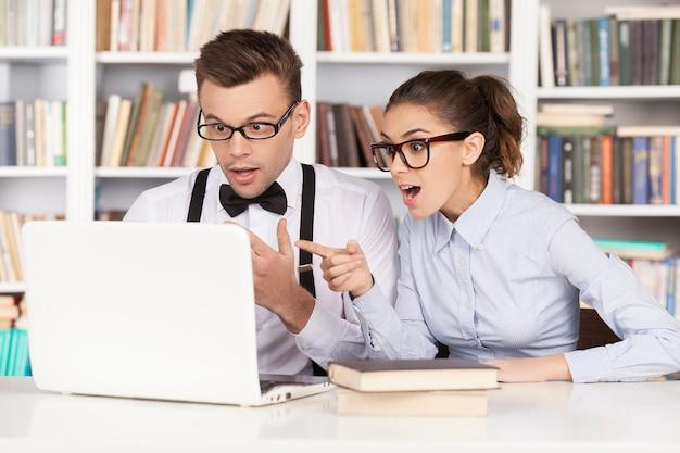 Coppia nerd. sorpreso giovane coppia nerd con gli occhiali che guarda il monitor del computer e tiene la bocca aperta mentre si è seduti insieme in biblioteca