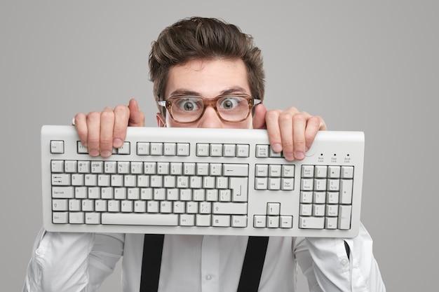 Nerd con gli occhiali con tastiera in studio