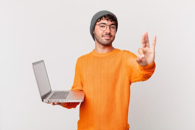 Uomo nerd con il computer che sorride e sembra amichevole, mostra il numero tre o il terzo con la mano in avanti, conto alla rovescia