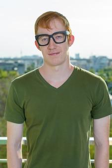 Uomo nerd con i capelli rossi che indossa occhiali da vista contro la vista della città