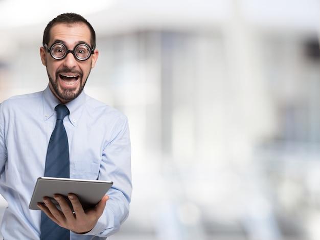 Uomo d'affari nerd che tiene una compressa grande copia-spazio luminoso