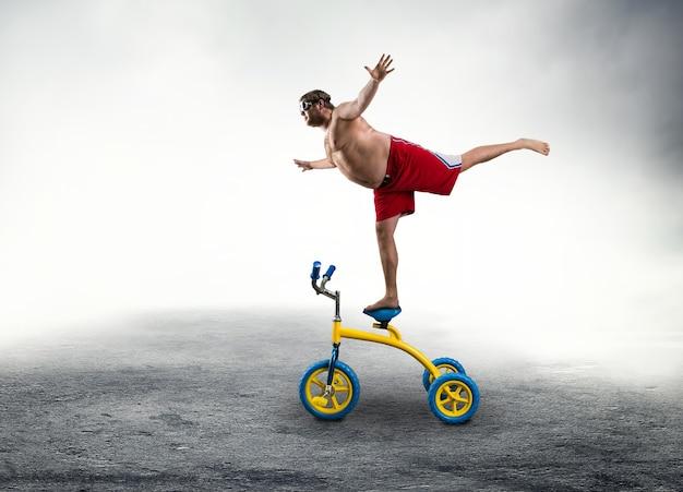 Uomo nerd in piedi su una piccola bicicletta