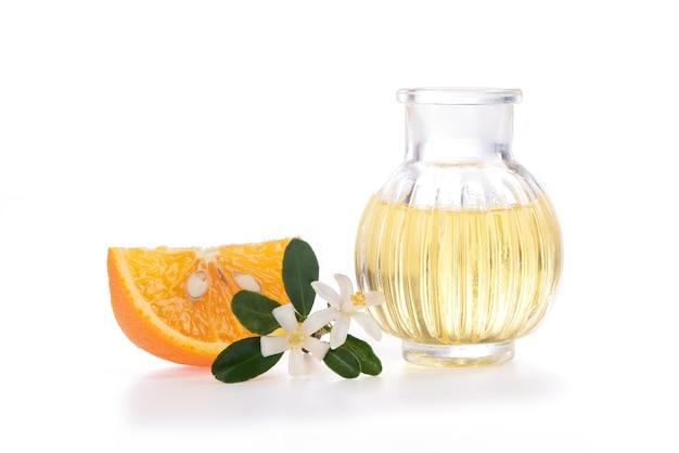 Olio essenziale di neroli, frutta e fiori su sfondo bianco.