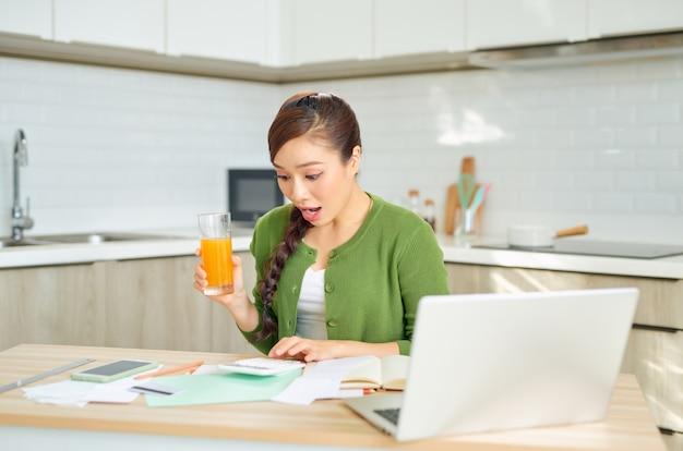 Giovane donna asiatica nervosa che esamina i suoi debiti finanziari in cucina a casa