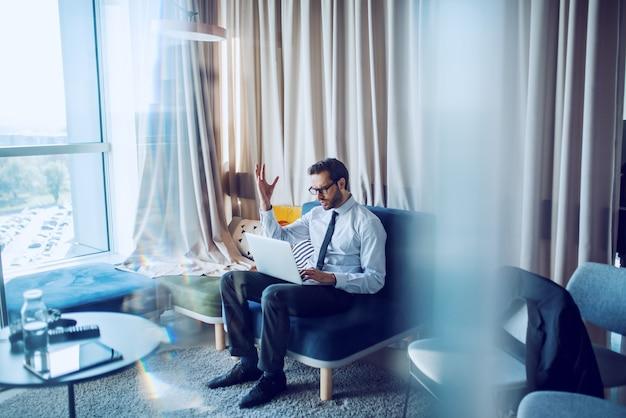 Uomo d'affari caucasico attraente nervoso in camicia e cravatta seduto in ufficio moderno sul divano e utilizzando il computer portatile.