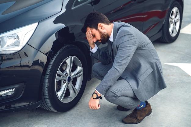 Uomo d'affari barbuto nervoso accovacciato accanto alla sua auto e tenendo la testa. il pneumatico è piatto. come arrivare in tempo per lavorare adesso?