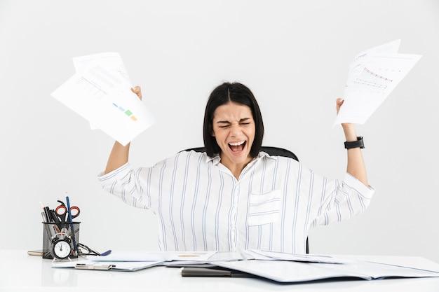 Imprenditrice bruna nervosa urlando e stressando mentre si lavora con documenti cartacei in ufficio isolato sopra il muro bianco