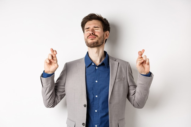 Uomo d'affari nervoso in vestito che implora dio, tenendo le dita incrociate con gli occhi chiusi, supplicando di vincere, esprimendo un desiderio su sfondo bianco.