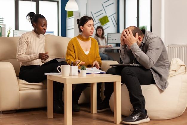 Uomini d'affari nervosi che urlano a vicenda seduti sul divano e colpiscono con gli appunti