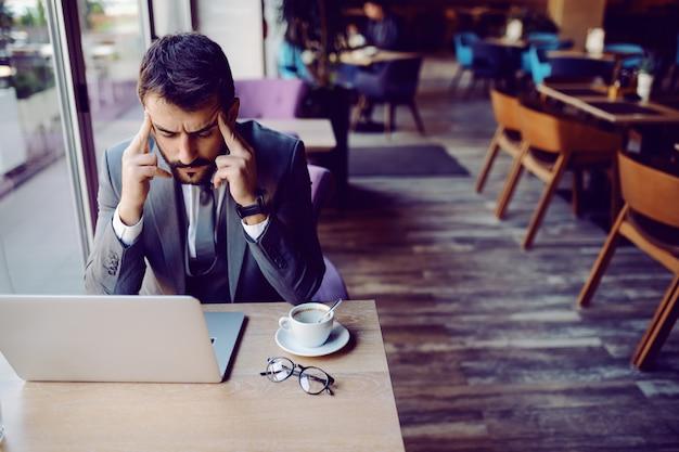 Uomo d'affari barbuto bello caucasico nervoso in vestito che si siede nella caffetteria e che tiene la testa. sul tavolo ci sono laptop, caffè e occhiali da vista. problemi al lavoro.