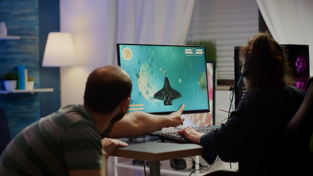 Coppia nervosa di giocatori informatici che urlano perdendo il gioco sparatutto spaziale durante il torneo di gioco giocando su un potente personal computer indossando cuffie professionali che si esibiscono in competizione cybersport