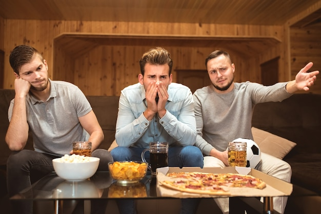 Gli amici nervosi guardano una partita di calcio vicino al tavolo con un cibo