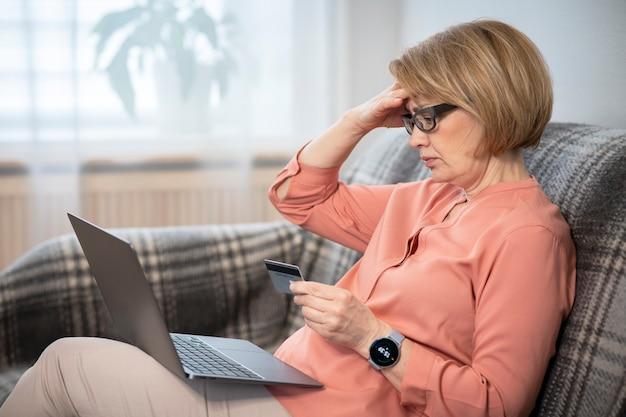 Nervoso orrore confuso anziano anziano pensionato donna, stressato preoccupato triste frustrato signora che ha problemi con il pagamento, l'acquisto in linea