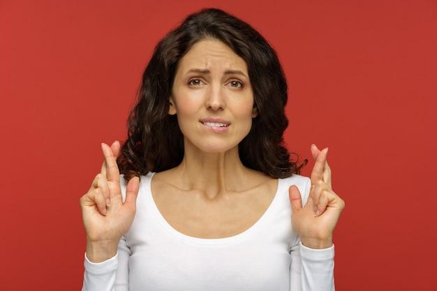 La donna nervosa che prega con le dita incrociate che morde il labbro vuole vincere la speranza di successo e buona fortuna