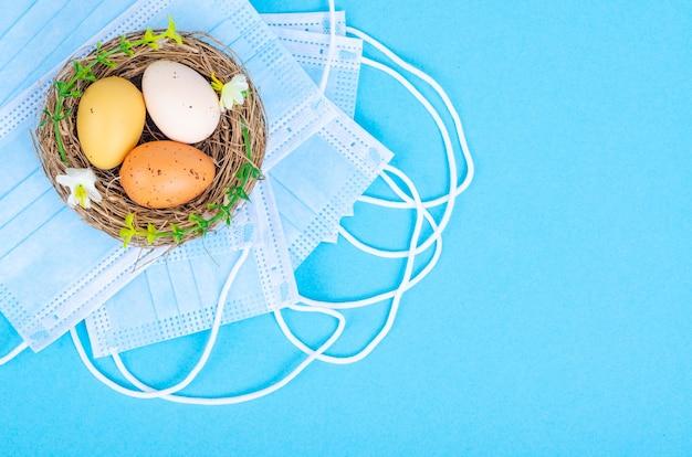 Nido con uova colorate con maschere mediche su superficie blu