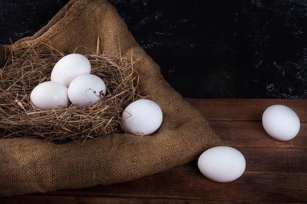 Un nido con uova bianche e uova viene lasciato cadere dal nido.