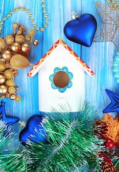 Scatola di nidificazione e decorazioni natalizie su sfondo blu