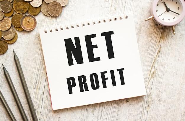 Net profit testo su un foglio di blocco note. le monete sono sparse.