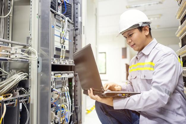 Amministratore di rete che tiene il laptop in mano funzionante configurazione con interruttore principale sull'armadio rack nel data center