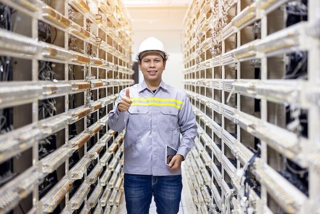 Ingegnere di rete che lavora con tablet nella sala del data center del server, tecnico specializzato professionale professional