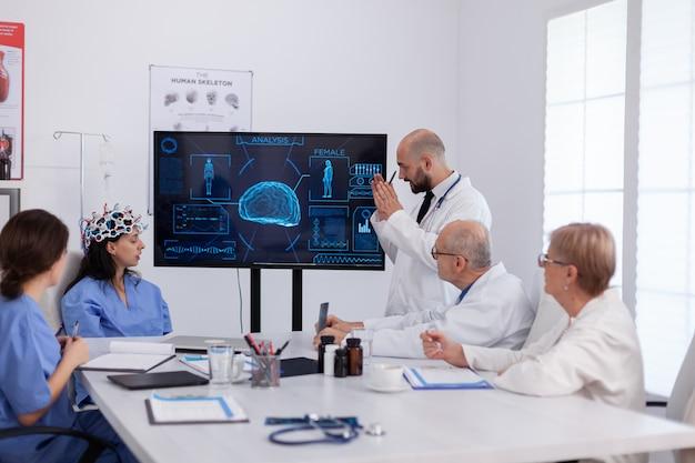 Neurologo che mostra la radiografia digitale ai colleghi medici che analizzano la presentazione della malattia cerebrale utilizzando l'alta tecnologia nella sala riunioni. team ospedaliero che analizza i maltrattamenti esaminando le competenze sanitarie