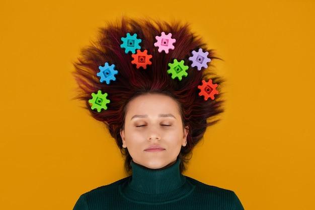 Neurofisiologia, neuroscienze, cervello, psicologia, salute mentale, creatività, concetto di idea. donna con ingranaggi nei capelli su sfondo arancione.