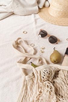 Composizione di moda neutra con accessori da donna e bigiotteria su coperta beige.