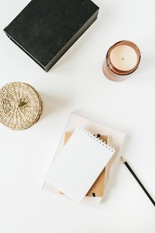 Area di lavoro minima neutra della scrivania dell'ufficio con il taccuino su bianco