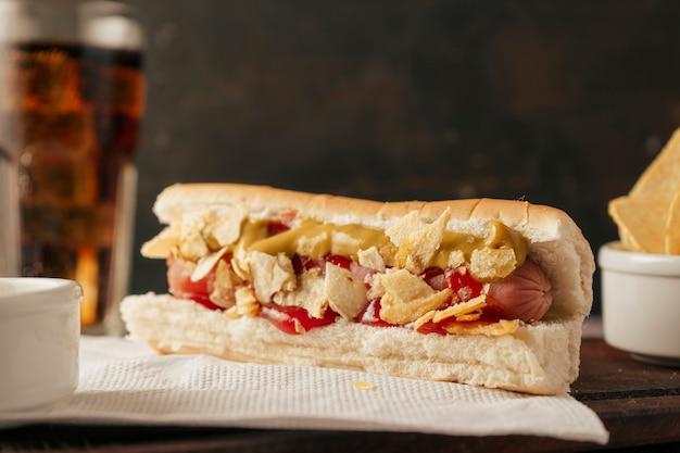 Vista neutra di un hot dog condito con senape, ketchup e condito con pezzi di patatine. vista orizzontale. concetto di cibo veloce e spazzatura.