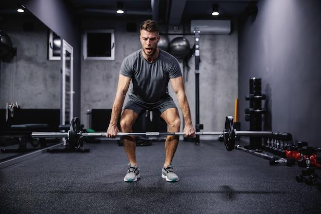 Mai arrendersi, forza e dinamica di movimento. un energico ragazzo muscoloso solleva pesi con pesi in palestra. un uomo forte sotto un grande sforzo fisico. sollevamento da terra, allenamento cross fit